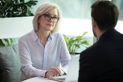 Mature hr manager listen applicant during job interview in office, looking at candidature with skepticism not sure that person is suitable for vacant position, client and bank worker meeting concept