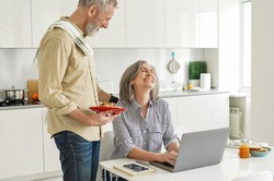 Mature husband bringing breakfast to happy wife working from home office. Older mid age man serving meal smiling senior woman helping with household while spouse using laptop sitting at kitchen table.
