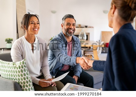 Mature indian man shaking hands with financial advisor at home. Happy smiling couple greeting broker with handshake at home. Multiethnic mid adult man and hispanic woman sealing a contract.