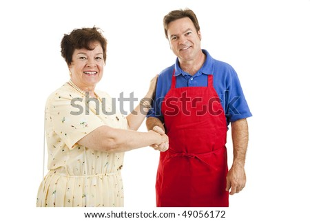 Mature lady shopping, shaking hands with a sales clerk or other type of worker.  Isolated on white.