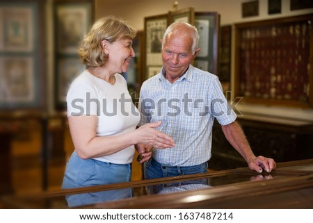 Mature male and female looking at exhibits In glass stands in historical museum