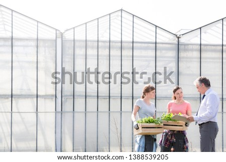 Mature male biochemist discussing with female coworkers against greenhouse #1388539205