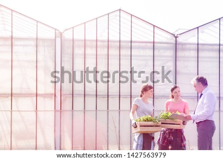Mature male biochemist discussing with female coworkers against greenhouse #1427563979