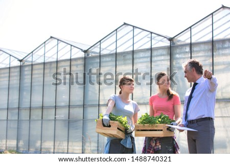 Mature male biochemist discussing with female coworkers against greenhouse #1488740321