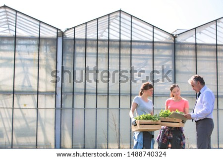 Mature male biochemist discussing with female coworkers against greenhouse #1488740324
