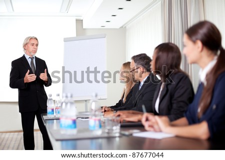 Mature male business executive training his associates during a meeting at office