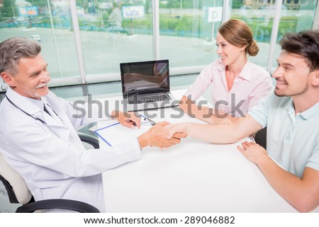 Mature male doctor greeting his new patients at clinic.