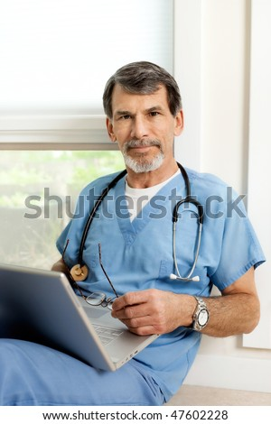 Mature male doctor seated on floor, working on laptop computer