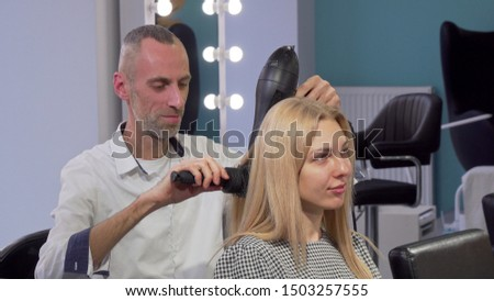Mature male hairdresser blow drying hair of a female client at the salon