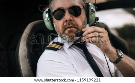 Mature male helicopter pilot with headset in the private helicopter. Close up of male pilot talking on the headset in the cockpit of a helicopter.