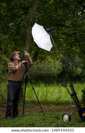 Mature male photographer gray beard glasses floppy hat brown shirt outside in green wooded area with DSLR digital camera on tripod testing umbrella strobe flash speedlite and flash exposure meter #1489144103