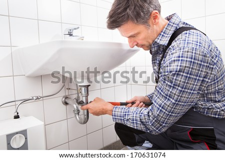 Mature Male Plumber Fitting Sink Pipe In Bathroom