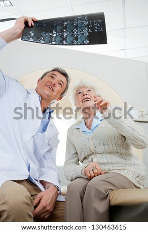 Mature male radiologist and senior female patient looking at x-ray