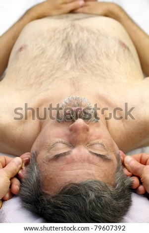 Mature male receiving ear reflexology massage of both ears at the same time.