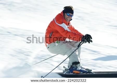 Mature male skier on ski slope, smiling toward camera, blurred motion