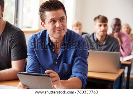 Mature Male Student With Digital Tablet In Adult Education Class
