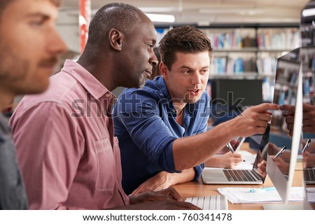 Mature Male Student With Tutor Learning Computer Skills
