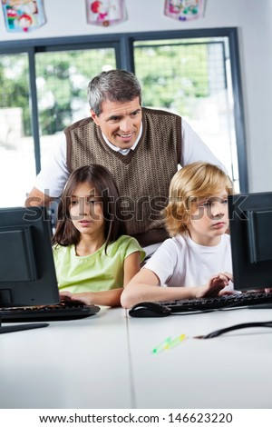 Mature male teacher looking at schoolchildren using desktop PC in computer lab