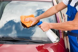 Mature male worker cleaning car windshield with cloth and spray bottle