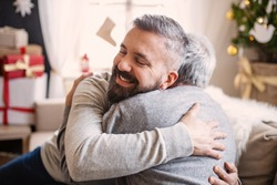 Mature man and senior father indoors at home at Christmas, hugging.