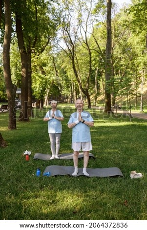 Mature man and woman with namaste do yoga on lawn grass