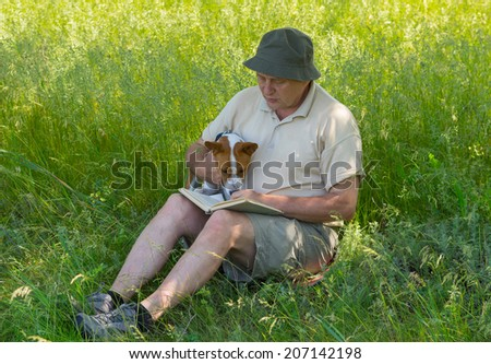 Mature man and young dog reading interesting book under tree shadow