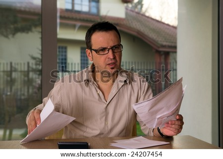 Mature man at home, calculation bills.