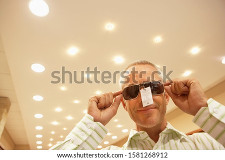 Mature man buying stylish sunglasses for summer vacation in shop with price label still attached