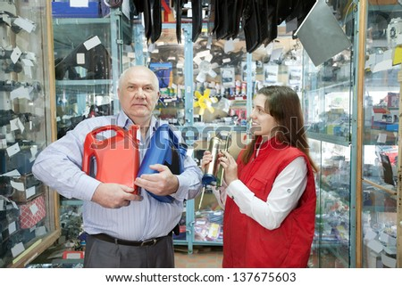Mature man buys motor oil in auto parts store