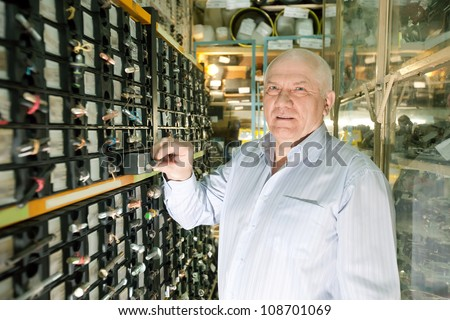 mature man chooses fasteners in  auto parts store