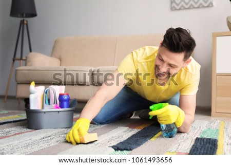 Mature man cleaning carpet at home #1061493656