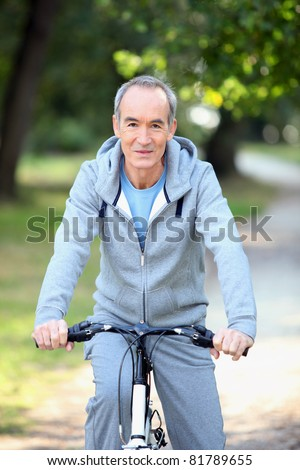 mature man doing bike in the forest