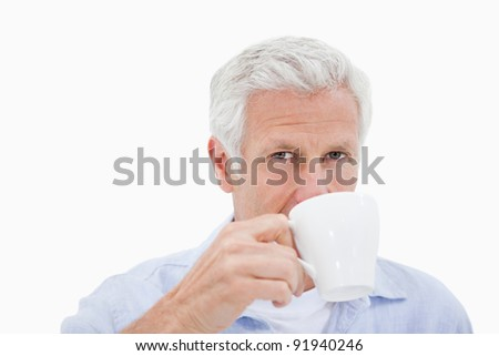 Mature man drinking tea against a white background