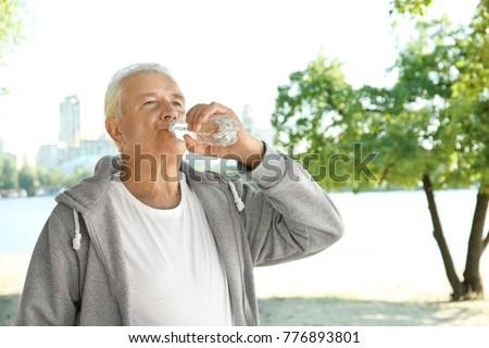Mature man drinking water on beach