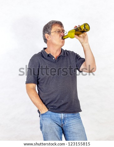 mature man drinks alcohol out of a bottle - stock photo