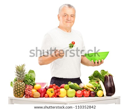 Mature man eating a salad, with fruits and vegetables on a table