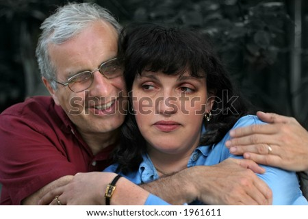 Mature man embracing his upset wife