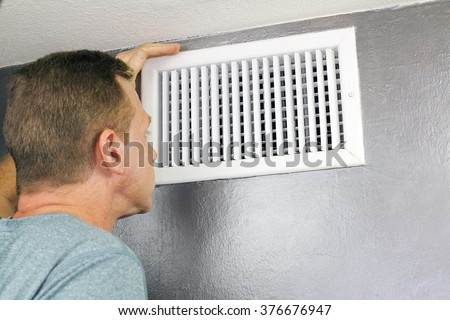Mature man examining an outflow air vent grid and duct to see if it needs cleaning. One guy looking into a home air duct to see how clean and healthy it is.