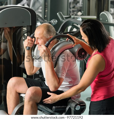 Mature man exercising at gym under supervision of personal trainer