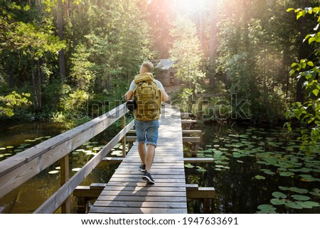 Mature man exploring Finnish nature in summer, walking across the bridge. Hiker with big backpack traveling in forests. Summer Scandinavian landscape of lakes and woods.