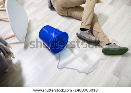 Mature Man Falling On Wet Floor In Front Spilled Bucket Of Water At Home Stock photo ©