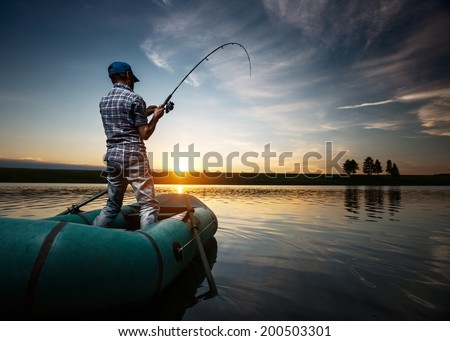Mature man fishing from the boat on the pond at sunset