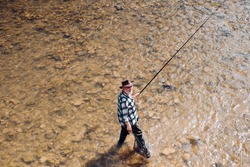 Mature man fishing on the pond. Happy fly fishing. Angler catching the fish. Master baiter. Catching and fishing. Rural getaway. Giving your hobby