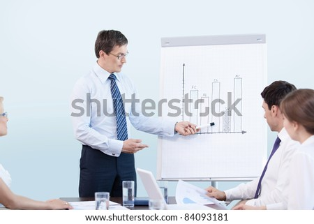 Mature man gives a presentation at the office