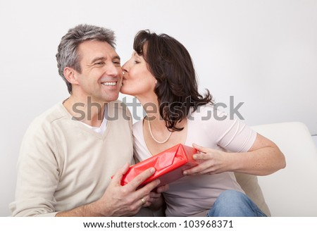 Mature man giving a present to his woman at home