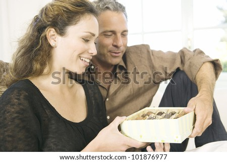 Mature man giving  a woman a box of chocolates at home.
