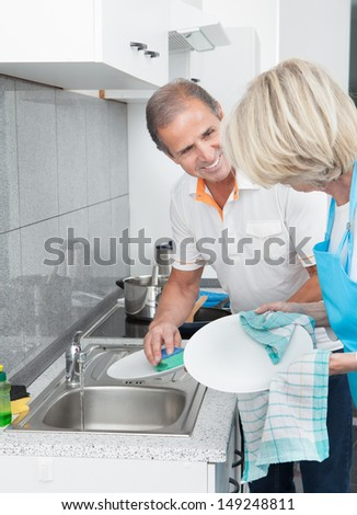 Mature Man Helping His Wife In Household Work - stock photo
