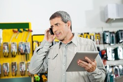 Mature man holding digital tablet while using mobilephone in hardware store