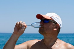 Mature man in cap and sunglasses drinking sparkling wine from glass in front of blue sea and sky on the beach