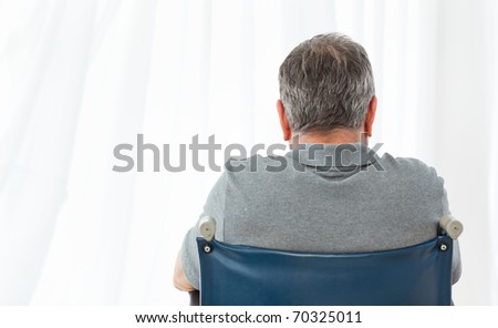 Mature man in his wheelchair with his back to the camera at home - stock photo